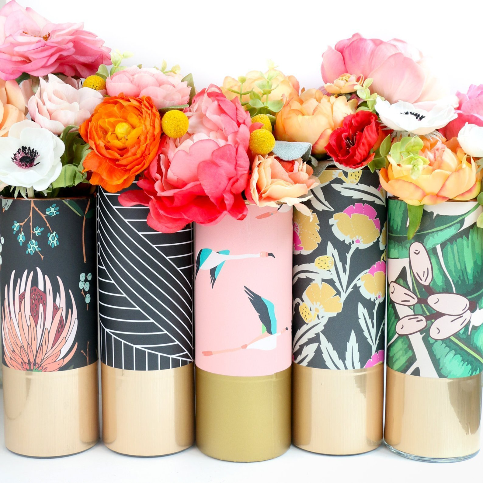 5 colorful flower vases filled with flowers