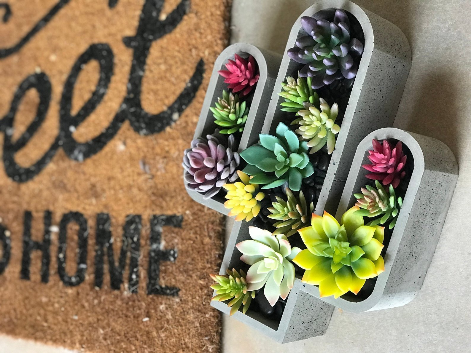 concrete planter in shape of cactus filled with succulents