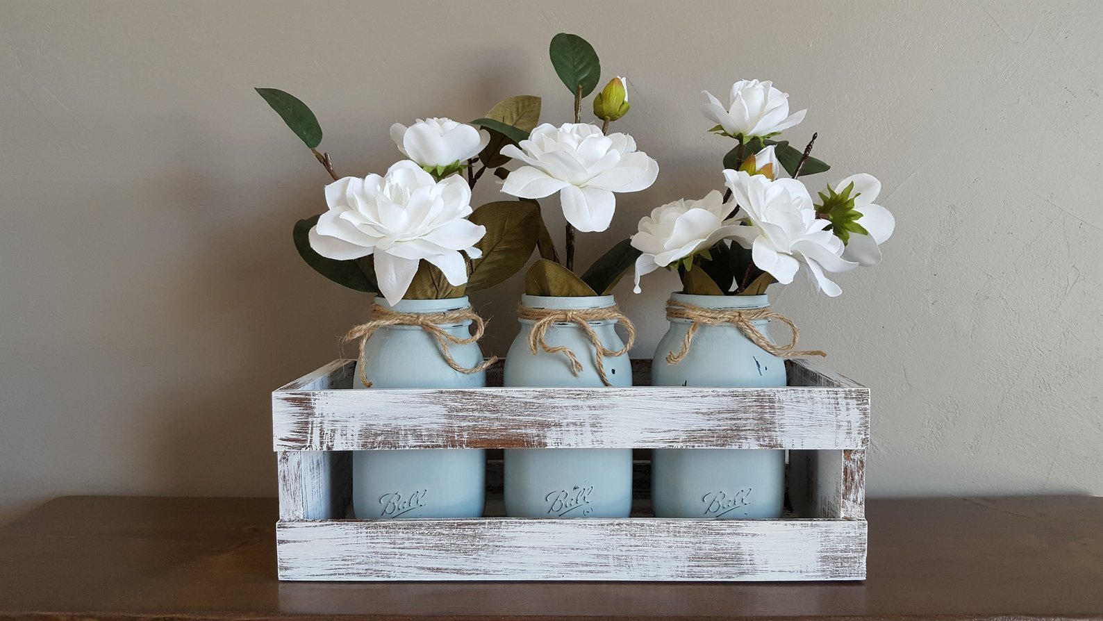 white washed wood crate with 3 blue mason jars and flowers