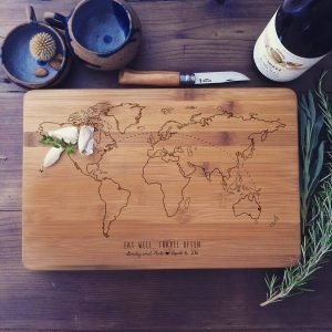 "wood cutting board with world map, words ""eat well, travel often"", names, and date engraved on it"