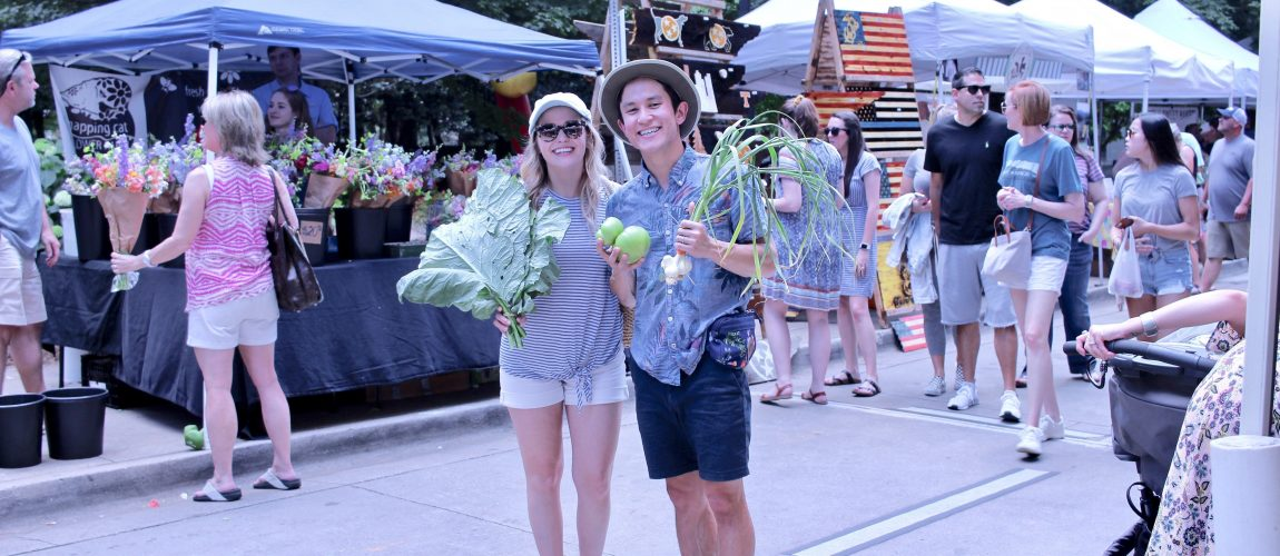 Chris and chelsea holding veggies at farmers market